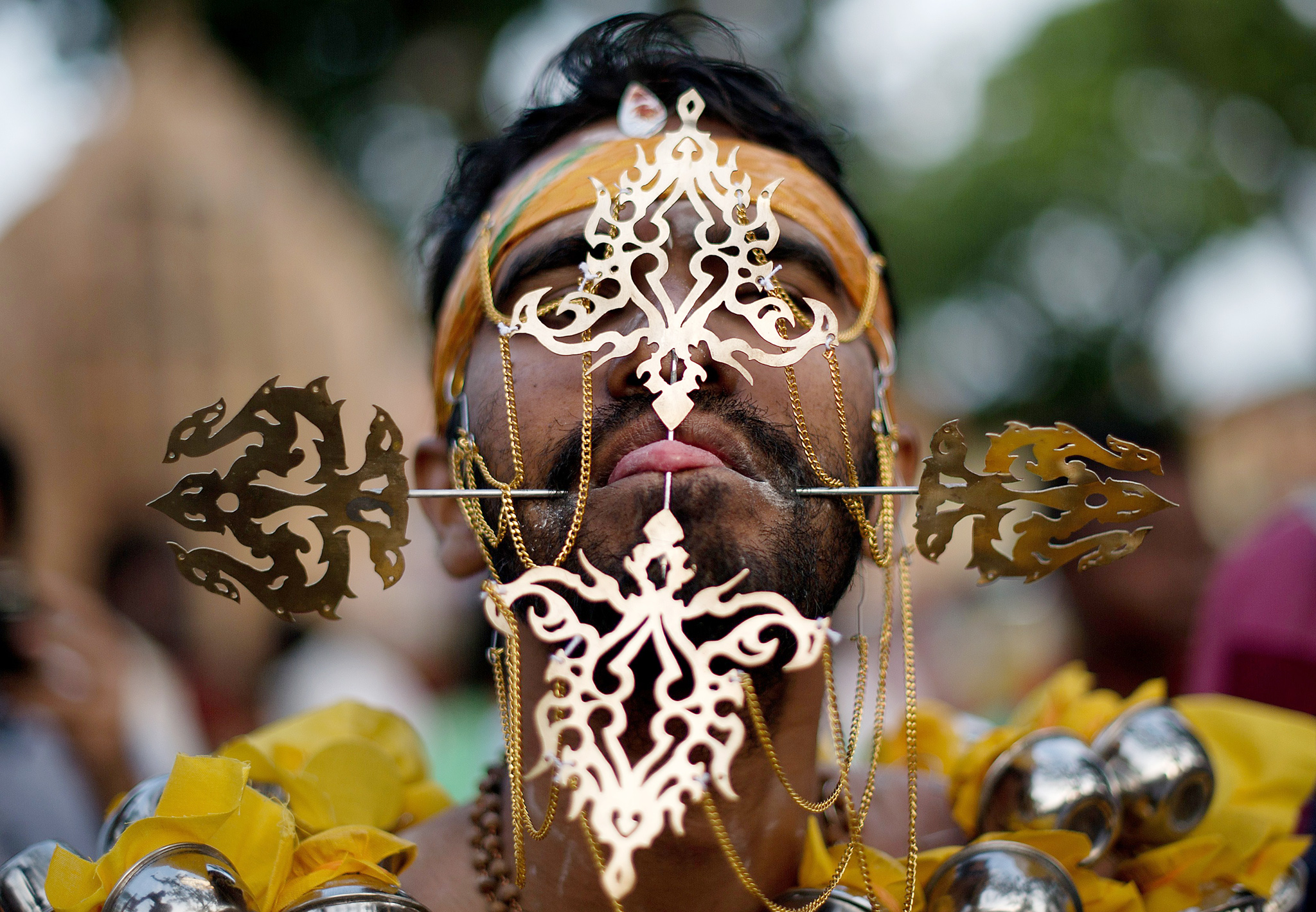 A Hindu devotee's tongue is pierced befo